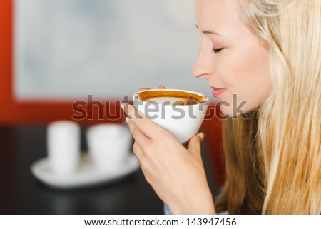 blond woman with closed eyes holding coffee cup in her hands - stock photo