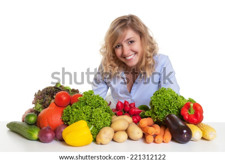 Blond woman with fresh vegetables looking at camera
