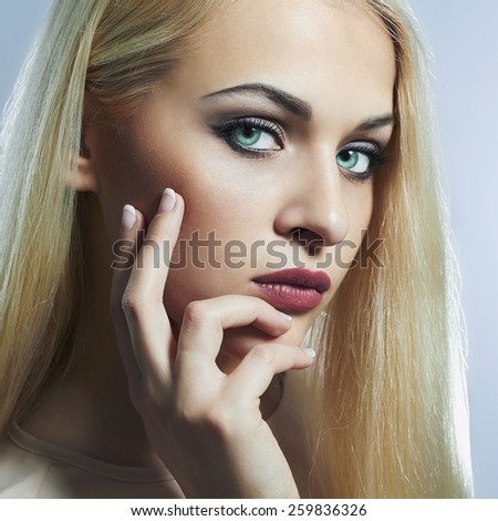 Blond woman with manicure.Beautiful girl model with blue eyes lens - stock photo