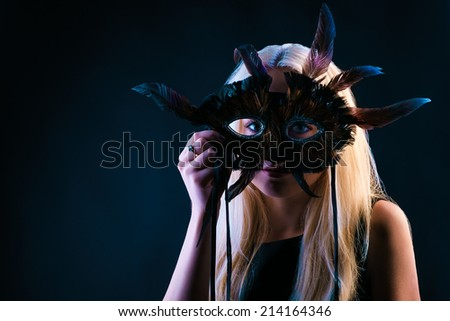 Blond Woman with Mask of Feathers in Low Key - stock photo
