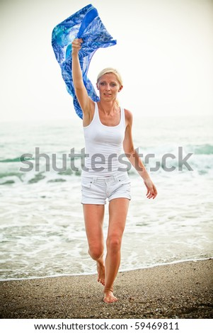 Blond woman with shawl relaxing near the sea