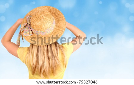 Blond woman with straw hat looking into blur sky - stock photo
