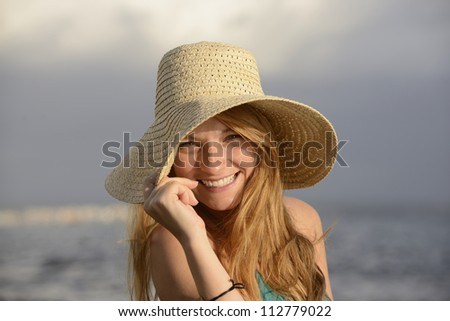 blond woman with sunhat on the beach laughing - stock photo