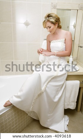 Blond young bride in sleeveless wedding dress with pearl detail and accessories getting ready in the bathroom - stock photo