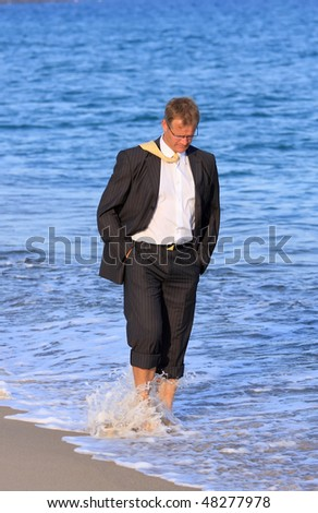 Blond , young businessman walks close to the sea - stock photo