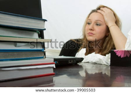 Blond young caucasian woman sitting at desk in front of laptop computer  with a box of tissues with focus on a pile of text books