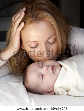 blond young mother with her baby lying in the bed
