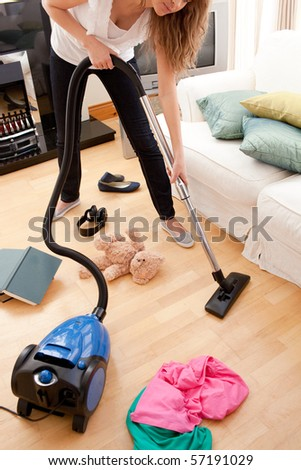 Blond young woman cleaning the living-room with a vacuum cleaner - stock photo