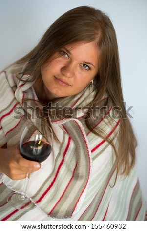 Blond young woman covered with a blanket, drinking red wine