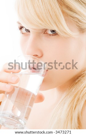blond young woman drinking a glass of water, close up, studio portrait on white - stock photo