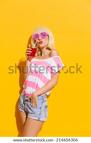 Blond young woman in pink sunglasses holding drinking a red drink. Three quarter length studio shot on yellow background. - stock photo