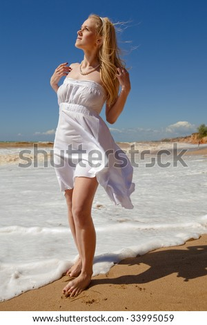 Blond young woman in white on seashore
