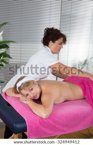 Blond young woman massage at spa center by a female therapist - stock photo