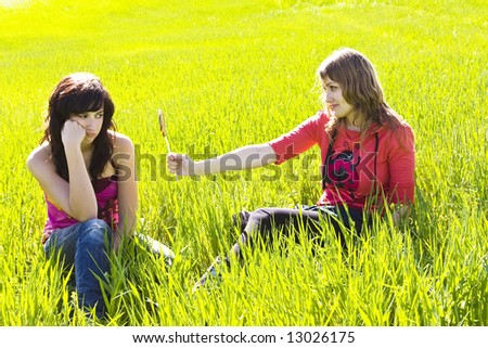 Blond young woman offering candy to her friend. - stock photo