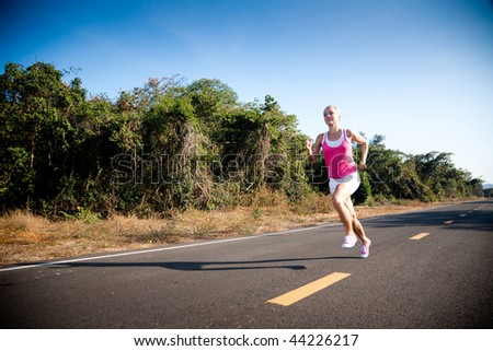 Blond young woman running cross country. Subject is blurred due to motion.