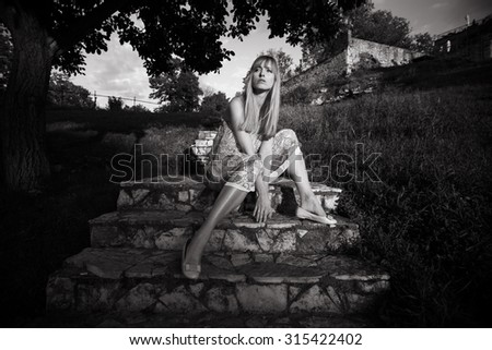 blond young woman sitting on the stairs in fashionable dress, full body shot, front view, outdoor shot, summer day at Kalemegdan, Belgrade