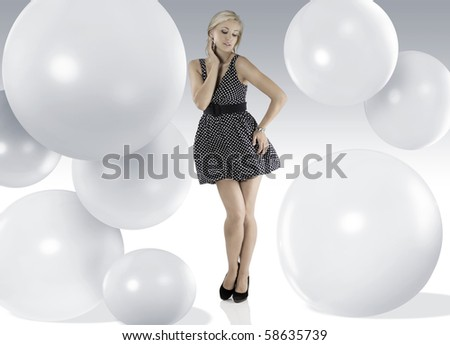 blond young woman wearing blue polka dot dress jewellery and taking pose