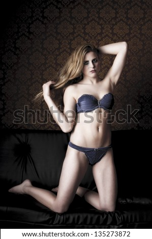 Blond young woman with long hair rolls around in blue lingerie on a black leather sofa. - stock photo