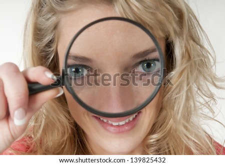 blond young woman with magnifying glass
