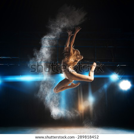 Blonde adult ballerina in jump on stage of theater with powder - stock photo