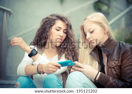 blonde and brunette beautiful stylish young women using smart phone in the city