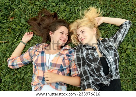 Blonde and brunette girl having rest on a grass - stock photo