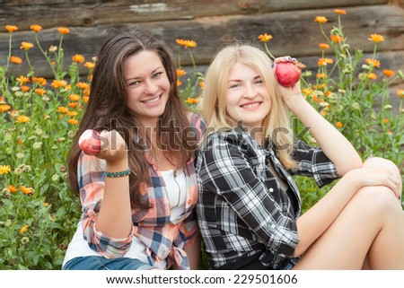 Blonde and brunette posing with ripe red apples - stock photo