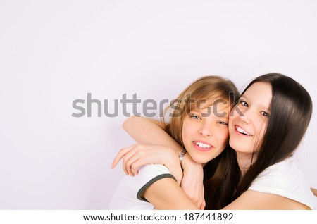blonde and brunette teen girls cuddling and laughing. light background. space for text. 11 years old girls in white clothes - stock photo