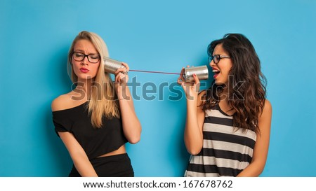 Blonde and brunette women talking with tin can telephone against blue background.  - stock photo