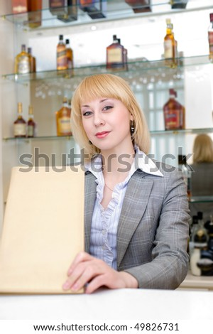 blonde barmaid at bar with wine list, copy space - stock photo