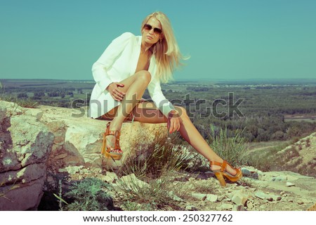 Blonde beautiful woman in white jacket on the rocks. Summer day