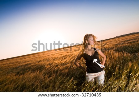 Blonde beauty in gold wheat field - stock photo