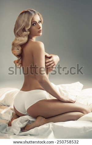 Blonde beauty posing on the bed - stock photo