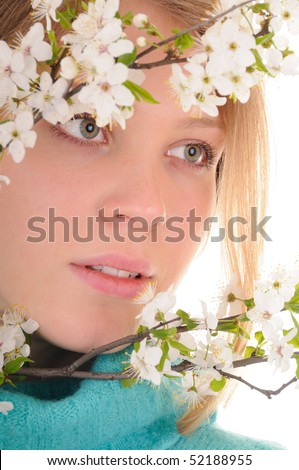 Blonde beauty woman behind spring white cherry flowers. Focus on woman's eyes. - stock photo