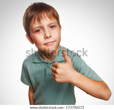 blonde blonde boy kid in blue shirt holding thumbs up, showing sign yes emotion isolated gray largeoy kid in blue shirt holding thumbs up, showing sign yes emotion isolated gray - stock photo