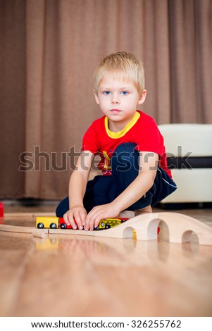 Blonde, blue-eyed little boy of five years in the red T-shirt barefoot beside the couch at home fun playing with wooden railway