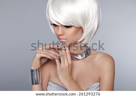 Blonde Bob Hairstyle. Fashion beautiful young girl in luxurious jewelry isolated on grey background. Fringe. Vogue Style. - stock photo