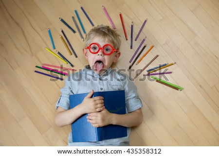 blonde boy in red shirt in glasses with a book lying on the floor next to the colored pencils and teased - stock photo
