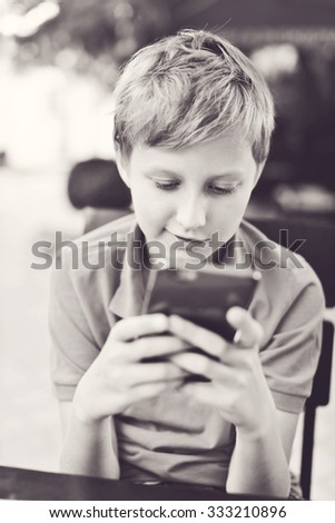 blonde boy playing phone in outdoor cafe - stock photo
