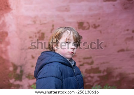 Blonde boy portrait outdoors in winter. Boy is looking at camera. - stock photo