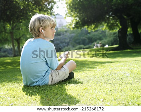 Blonde boy sitting on grass in park, listening to MP3 player, side view - stock photo