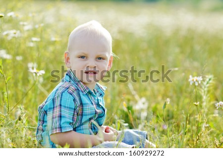blonde boy sitting on the meadow - stock photo