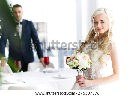 blonde bride and brunette groom in resturant near white windiw - stock photo