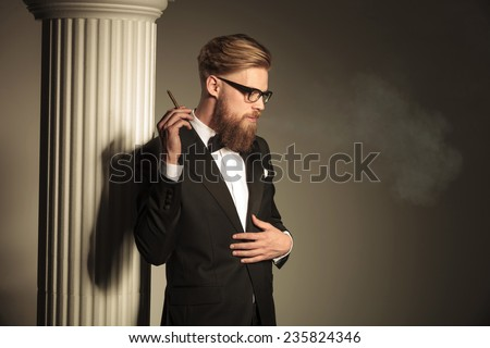 Blonde business man looking down while holding a cigarette in his right hand. He is fixing his suit with his left hand. - stock photo