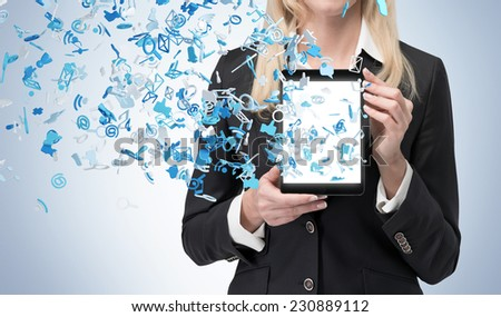 Blonde business woman holding a tablet with flying social networking icons. Blue background.