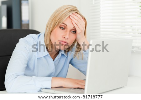 Blonde business woman touching her forehead being tired in her office