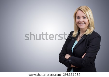 Blonde business woman with crossed hands looking in to camera on clean grey background - stock photo