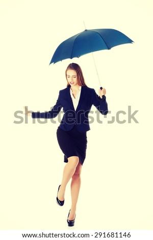 Blonde businesswoman dancing with umbrella - stock photo