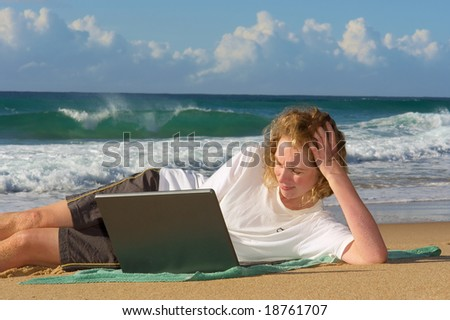 Blonde businesswoman lies with notebook on beach - sunrise light. Shot in Sodwana Bay Nature Reserve, KwaZulu-Natal province, Southern Mozambique area, South Africa. - stock photo