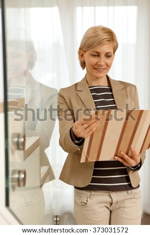 Blonde businesswoman looking at folder holding in hands, standing by stairs. - stock photo